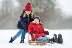 Twee grappige meisjes die pret met een ar in mooi de winterpark hebben Leuke kinderen die in een sneeuw spelen stock fotografie