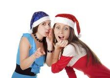 Twee grappige meisjes in kappen van Santa Claus die in de camera kijken royalty-vrije stock fotografie