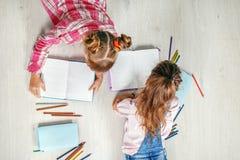 Twee grappige meisjes lezen en schrijven Stock Afbeeldingen