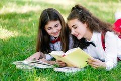 Twee grappige schoolmeisjes liggen op het gras en lezen boeken De meisjes, meisjes, zusters worden onderwezen lessen in aard stock foto's