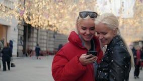 Twee grappige vrienden die selfie in openlucht in de straat bij zonsondergang met een warm licht op de achtergrond nemen, meisjes stock video