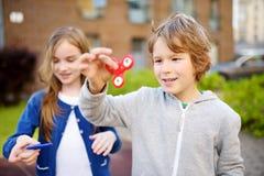 Twee grappige vrienden die spelen met friemelen spinners op de speelplaats Populair spanning-verlichtend stuk speelgoed voor scho stock afbeelding