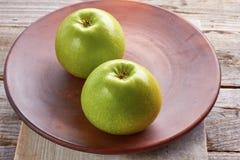 Twee groene appelen op ceramische plaat Royalty-vrije Stock Fotografie