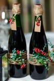 Twee groene huwelijksflessen met rode die wijn met bloemen wordt verfraaid, Royalty-vrije Stock Foto's