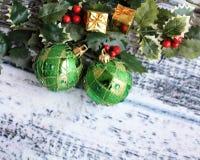 Twee groene Kerstmisballen en Hulstbladeren Royalty-vrije Stock Fotografie