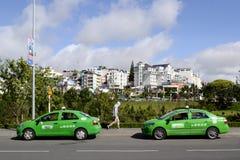 Twee groene taxiauto's op de weg Royalty-vrije Stock Afbeeldingen