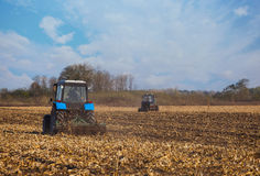 Twee groot blauw tractorploeg geploegd land na het oogsten van het maïsgewas Stock Foto