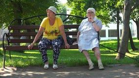 Twee grootmoeders in hoofddeksels zitten op een bank op een de zomerdag stock videobeelden
