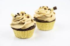 Twee grote en heerlijke muffins die met karamelschuim en zoete buis worden verfraaid royalty-vrije stock afbeeldingen