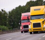 Twee grote installatie semi vrachtwagens die zij aan zij op de weg lopen Royalty-vrije Stock Afbeeldingen