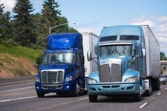 Twee grote installaties semi vrachtwagens in blauwe toon en verschillende modellen met stock afbeelding