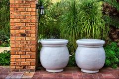 Twee grote potten naast baksteenkolom Royalty-vrije Stock Afbeeldingen