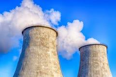 Twee grote rokende pijpen van krachtcentrale Zware witte rook op blauwe hemelachtergrond royalty-vrije stock fotografie