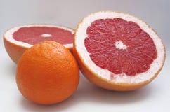 Twee halfs van rode druivenfruit en een sinaasappel Royalty-vrije Stock Afbeelding