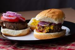 Twee hamburgers op een plaat, één open gezicht stock foto