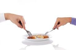 Twee handen, één aardappelpannekoek Stock Afbeeldingen