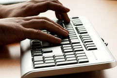 Twee handen die aan het toetsenbord werken Stock Afbeelding