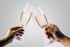 Twee handen die champagne roosteren stock fotografie