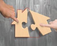 Twee handen die de raadsels van de blokhuisvorm assembleren Stock Fotografie