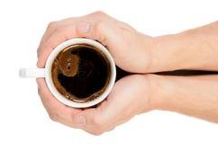 Twee handen die een kop van verse koffie houden. Stock Foto's