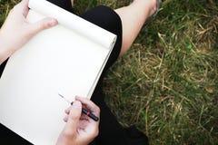 Twee handen die een potlood en een album voor openlucht trekken houden stock afbeeldingen