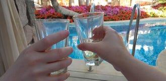 Twee handen die glazen met witte wijnstok samen over blauwe pool houden stock afbeelding