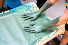 Twee handen die groene acrylverf op een stuk van Witboek bevlekken Stock Afbeeldingen