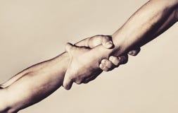 Twee handen, die hand van een vriend helpen Handdruk, wapens, vriendschap Vriendschappelijke handdruk, vrienden die, groepswerk b royalty-vrije stock afbeelding