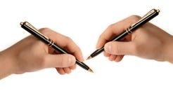 Twee handen die op Witboek schrijven Stock Foto