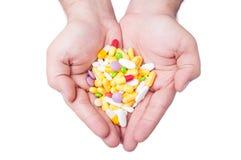 Twee handen die pillen houden stock afbeelding