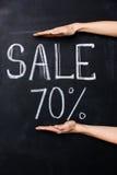 Twee handen die zeventig die percentenverkoop tonen op bord wordt getrokken Stock Afbeeldingen
