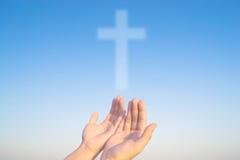 Twee handen en kruis van Christus en gelovigen Stock Afbeeldingen