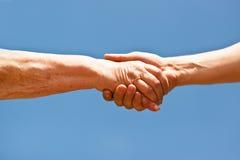 Twee handen het schudden overhandigt blauwe hemel Royalty-vrije Stock Foto's