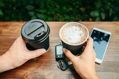 Twee handen houden koppen van koffie op de houten lijst Stock Fotografie