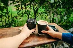 Twee handen houden koppen van koffie op de houten lijst Stock Afbeelding