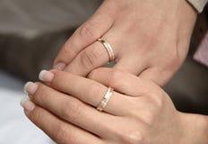 Twee handen met ringen op huwelijkendag stock afbeeldingen