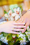 Twee handen met trouwringen op het bloemboeket Royalty-vrije Stock Afbeeldingen