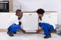 Twee Handige Mensen die de Afwasmachine In The Kitchen bevestigen royalty-vrije stock fotografie