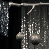 Twee hangende zilveren Kerstmisballen op donkere en zilveren achtergrond stock foto's