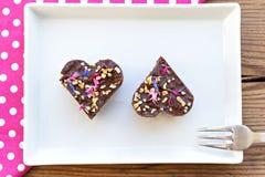 Twee hart gestalte gegeven stukken van de chocoladecake op witte plaat Royalty-vrije Stock Afbeeldingen