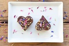 Twee hart gestalte gegeven stukken van de chocoladecake op witte plaat Stock Foto's