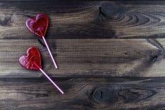 Twee hart gevormde lollys op houten lijst Stock Afbeelding