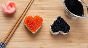 Twee hart gevormde sushi met zalmkuiten en beloega Royalty-vrije Stock Foto's