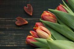 Twee harten en tulpenboeket op donkere houten planken Royalty-vrije Stock Foto