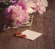 Twee harten op de witte lege kaart voor een inschrijving en een boeket van roze pioenen Stock Fotografie