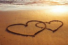 Twee harten op het zand Stock Foto's