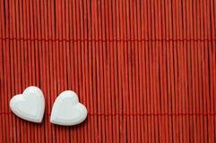 Twee harten op rood bamboe Stock Fotografie