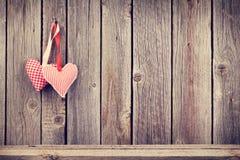 Twee harten van de Valentijnskaartendag op rustieke houten muur