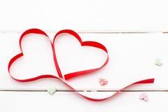 Twee harten van rood lint en sommige kleine harten op witte houten achtergrond Royalty-vrije Stock Foto
