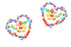 Twee harten van weinig kleurrijke suikergoedharten Gekarameliseerde bloemen Geïsoleerd op een witte achtergrond Royalty-vrije Stock Afbeelding